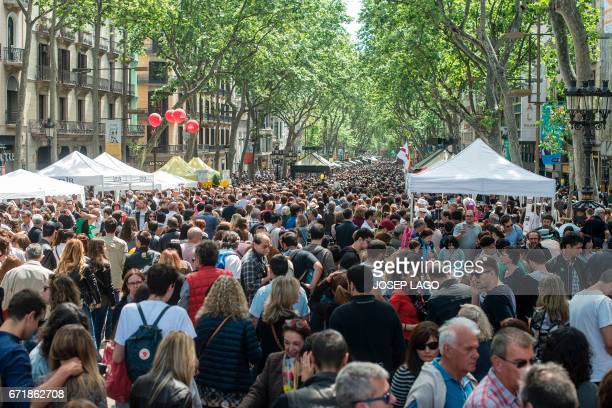 People stroll on Las Ramblas in Barcelona on April 23 2017 on Saint George's day Traditionally men give women roses and women give men a book to...