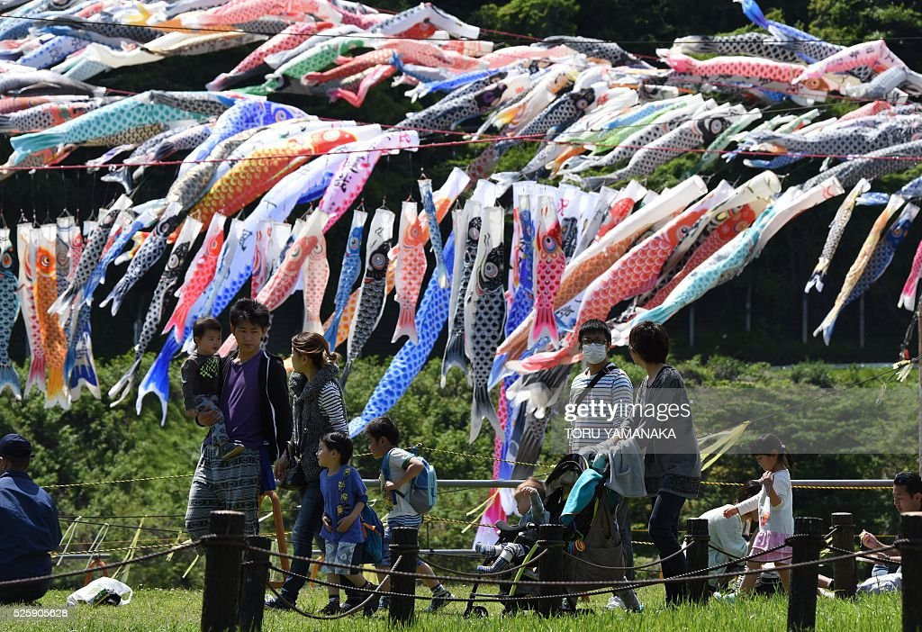 People stroll under carp streamers fluttering in a riverside park in Sagamihara, suburban Tokyo, on April 29, 2016 ahead of May 5 Children's Day in Japan. Some 1,200 carp streamers were hoisted over the Sagami River to celebrate the annual holiday of Children's Day - part of Japan's 'Golden Week' holiday which is traditionally one of the busiest travel times of the year. / AFP / TORU