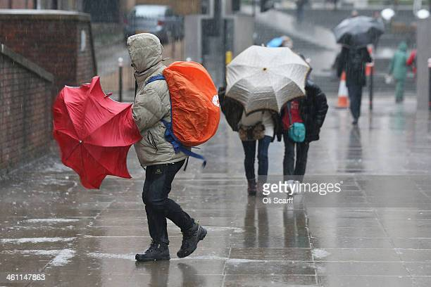 People struggle in rain and strong winds near St Paul's Cathedral on January 7 2014 in London England Over 100 areas of the UK have been warned by...