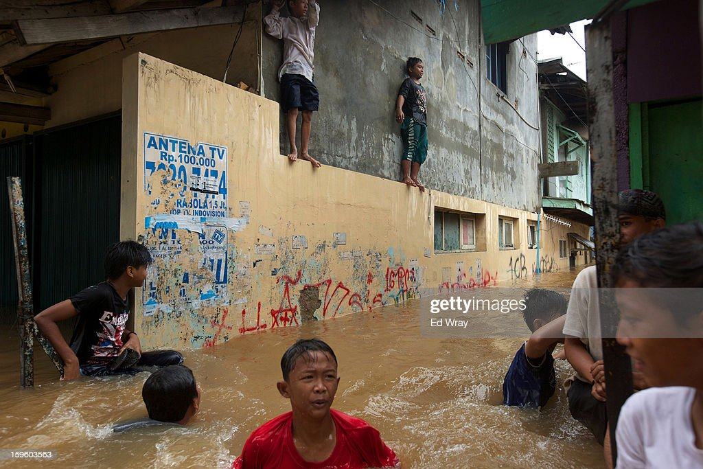 People struggle through floodwaters in Jakarta's central business district on January 17, 2013 in Jakarta, Indonesia. Thousands of Indonesians were displaced and the capital was covered in many key areas in over a meter of water after days of heavy rain.
