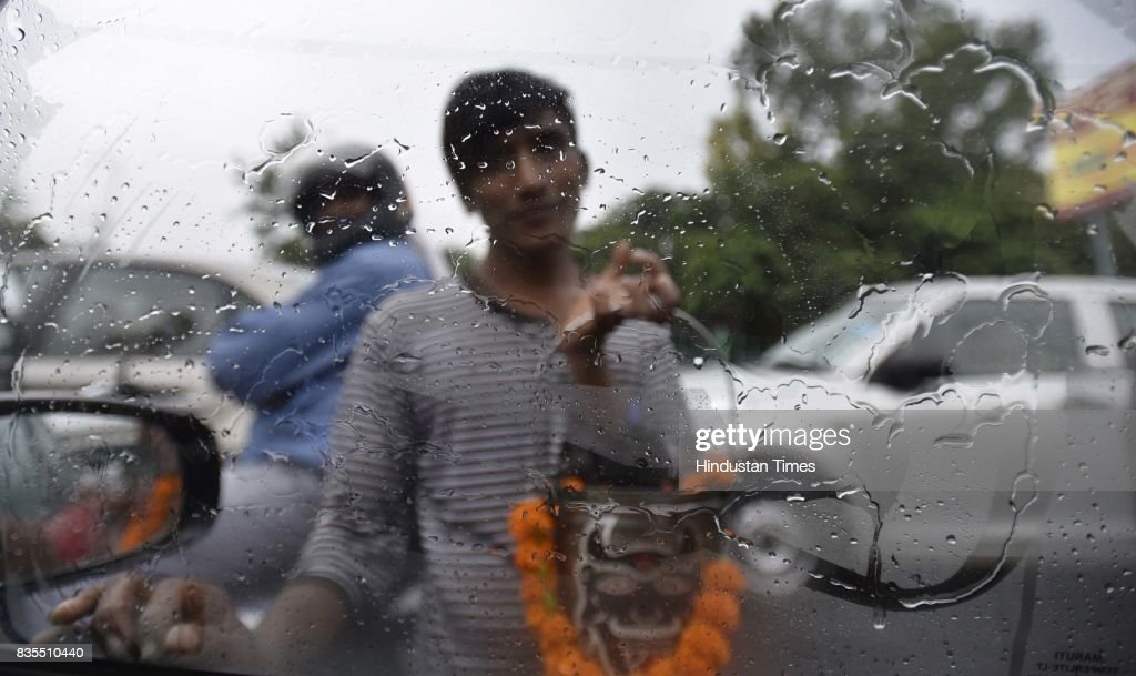 People stuck at Halli Road during the rain, on August 19, 2017 in New Delhi, India. Delhi received showers early morning which brought temperatures down to a comfortable 26 degrees Celsius. The India Meteorological Department (Met) officials said that there might be thunderstorm with showers later in the day while the maximum temperature is likely to be around 34 degrees Celsius.