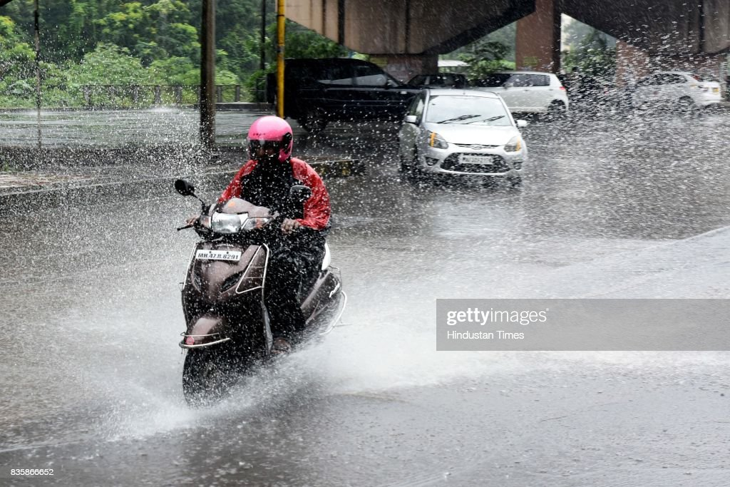 People stuck during the rain at Uran Phata Nerul, on August 19, 2017 in Mumbai, India. These weather conditions have been attributed to the presence of a low pressure which is currently lying over the Vidarbha region. Due to this, moisture incursion has increased over Mumbai as well as Thane and the cities have recorded these heavy spells.