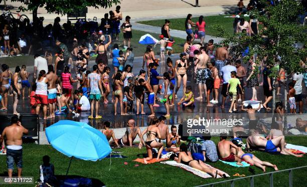 People sunbath and cool off in fountains on a bank of the river Manzanares in Madrid on June 18 as temperatures rose high across Spain Spain goes...