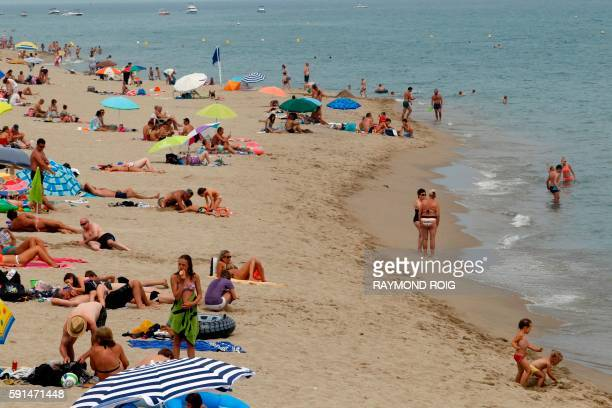 People sunbath and swim on August 17 2016 at a beach in Leucate where 'burkini' a fullbody swimsuit designed for Muslim women is probihibited by an...