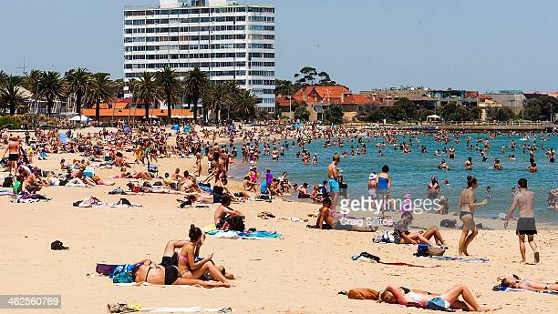 People sunbath as they enjoy the warm weather at St Kilda Beach on January 14 2014 in Melbourne Australia Temperatures are expected to reach over 40...