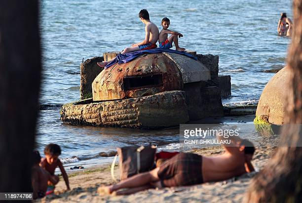 People sunbath atop of a decrepit communist era bunker on the shore in Qerret beach on July 13 2011 During its selfimposed isolation under the...