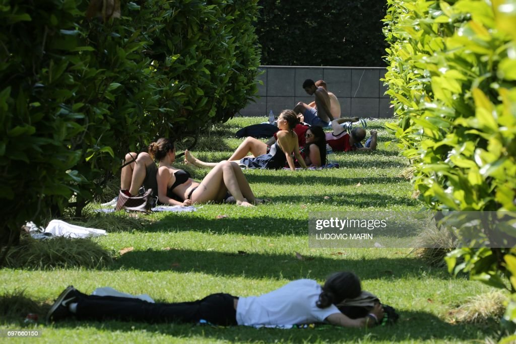 People sunbath near the Trocadero fountain in Paris, on June 19, 2017, as the French capital is placed on heatwave alert as temperatures are set to soar in the coming days. /