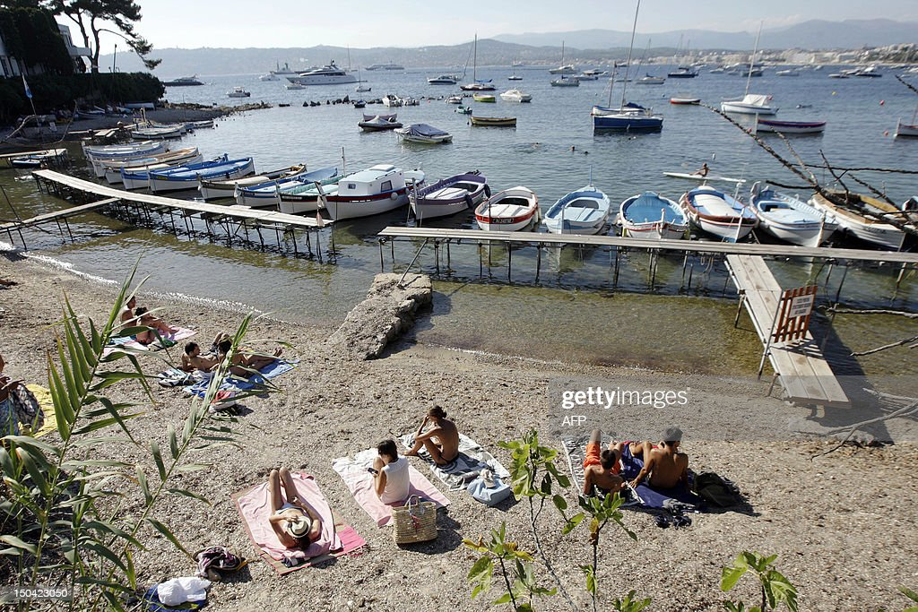 People sunbath on a beach in the French southeastern city of Juan les Pins, near Antibes, on August 15, 2012.