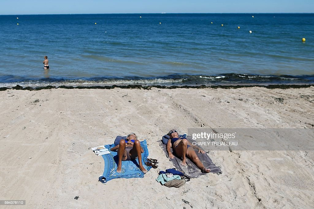 People sunbath on August 23 2016 in LucsurMer northwestern France A heat wave is expected to hit France from August 23 2016 / AFP / CHARLY TRIBALLEAU