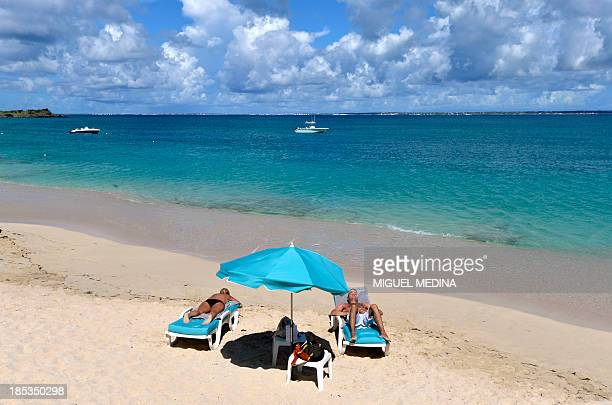 People sunbath on the beach in St Martin on the Caribbean Island of Guadeloupe on October 19 2013 AFP PHOTO / MIGUEL MEDINA