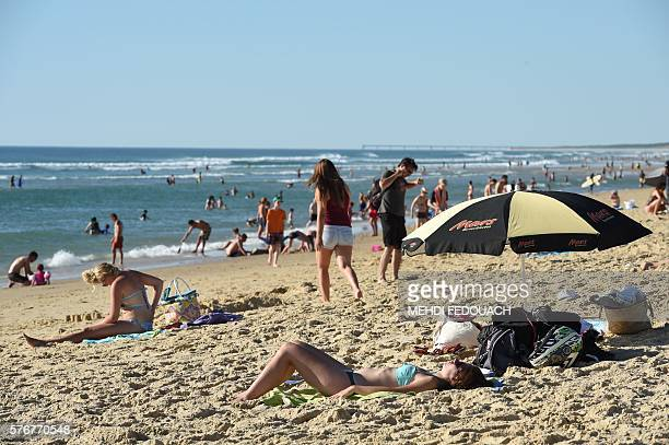 People sunbath on the beach on July 17 2016 in Biscarrosse southwestern France / AFP / Mehdi FEDOUACH