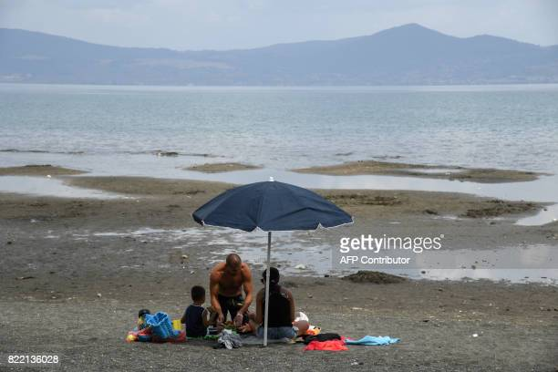 TOPSHOT People sunbathe along the shores of Lake Bracciano 32 km northwest of Rome as the Mayor of Rome decided whether or not to ration drinking...