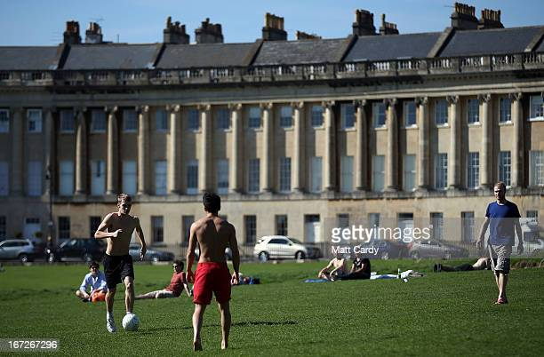 People sunbathe and play football in the spring sunshine in front of the Royal Crescent in Royal Victoria Park on April 23 2013 in Bath England After...