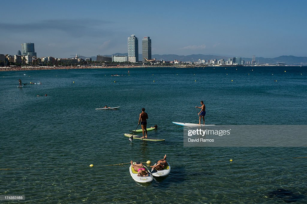 People sunbathe and practise stand up paddle surf at Barceloneta Beach on July 24, 2013 in Barcelona, Spain. Foreign visitors to Spain set a new record high in June surpassing six million tourists for the first time ever and climbing by 5.3 percent since June 2012.