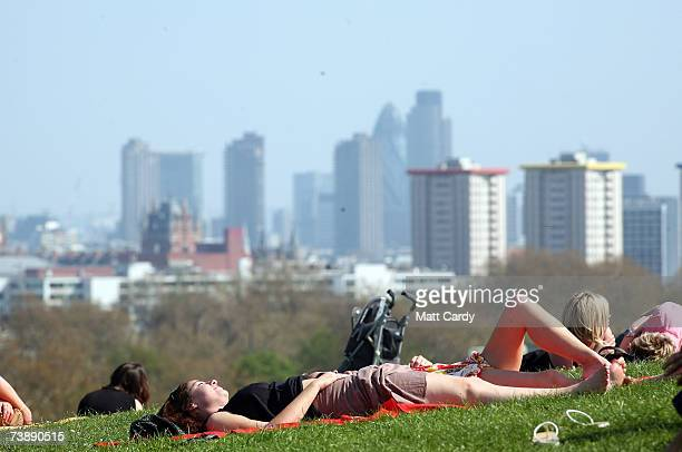 People sunbathe as they enjoy the hot weather in Primrose Hill on April 15 2007 in London England The unseasonably warm weather has heralded the...