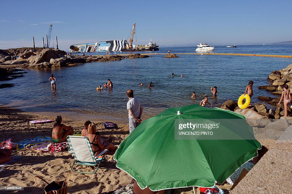 People sunbathe as workers of the U.S. firm Titan Salvage and Italian firm Micoperi work on salvaging the Costa Concordia, near the harbour of Giglio Porto on June 23, 2012. Salvage crews began preliminary work this week on preparations to refloat the half-submerged Costa Concordia cruise liner in what is set to be the biggest ever operation of its kind. The cruise liner, operated by Carnival Corp's Costa Cruises unit, capsized off the Tuscan island of Giglio after hitting rocks on January 13. At least 30 people died and two are still unaccounted for.