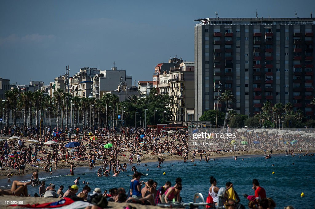 People sunbathe at Barceloneta Beach on July 24, 2013 in Barcelona, Spain. Foreign visitors to Spain set a new record high in June surpassing six million tourists for the first time ever and climbing by 5.3 percent since June 2012.Ê