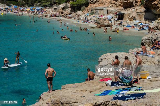 People sunbathe at Cala Salada beach on August 21 2013 in Ibiza Spain The small island of Ibiza lies within the Balearics islands off the coast of...