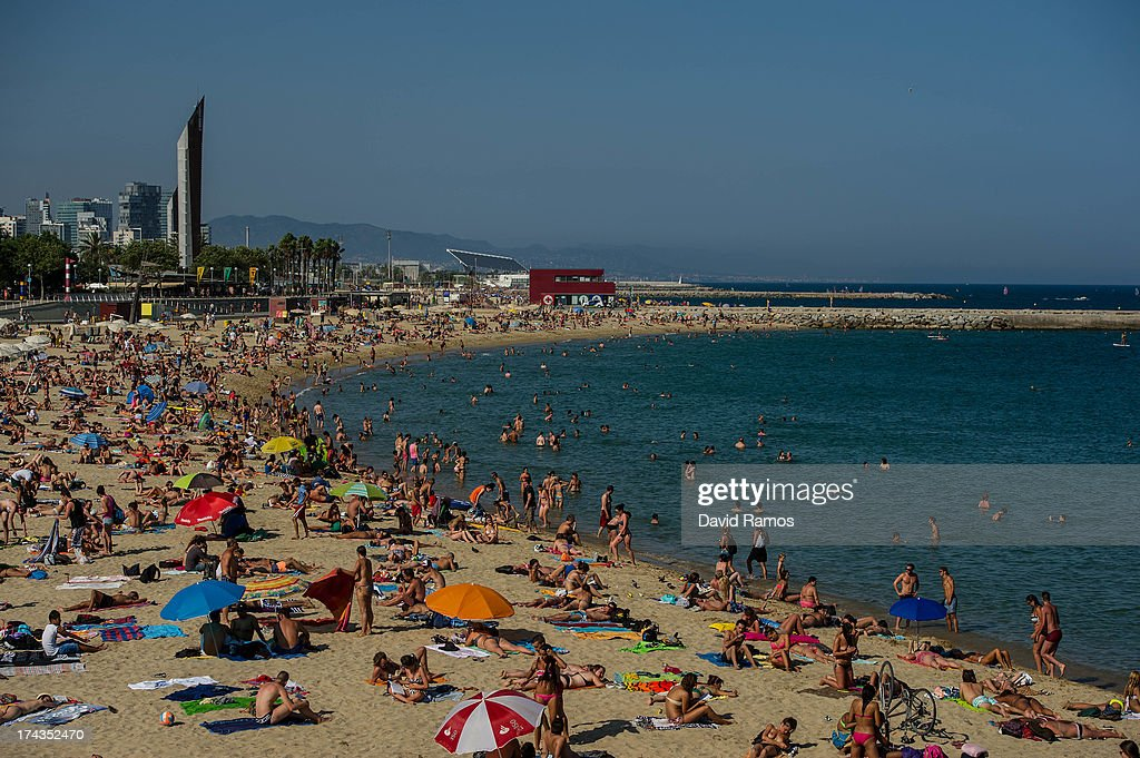 People sunbathe at the Mar Bella Beach on July 24, 2013 in Barcelona, Spain. Foreign visitors to Spain set a new record high in June surpassing six million tourists for the first time ever and climbing by 5.3 percent since June 2012.
