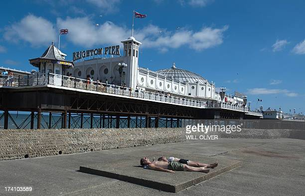 People sunbathe below Brighton Pier on the south coast during hot weather on July 20th 2013 Britain has been experiencing hot weather this month with...