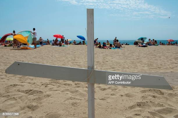 People sunbathe close to a cross on Barcelona's Bogatell beach during an action called by pro human rights organizations 'Tanquem els CIE' 'Immigrant...