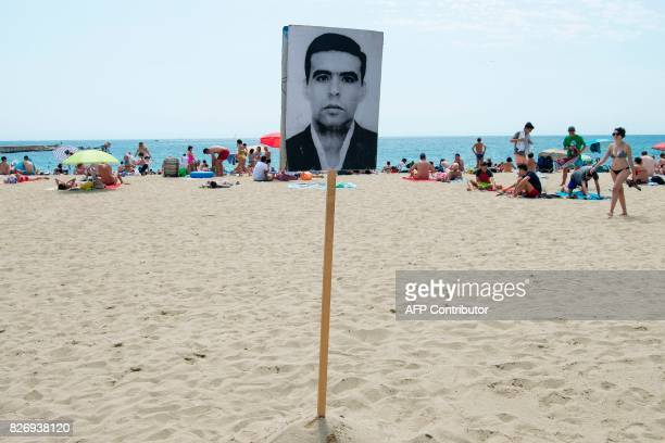 People sunbathe close to a photograph of a dead migrant on Barcelona's Bogatell beach during an action called by pro human rights organizations...