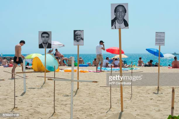 People sunbathe close to crosses and photographs of a dead migrants and refugees on Barcelona's Bogatell beach during an action called by pro human...