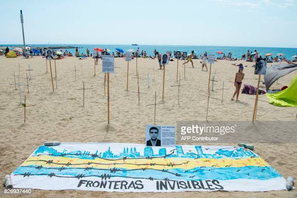 TOPSHOT People sunbathe close to crosses and photographs of a dead migrants and refugees and a banner reading 'Invisible frontiers' on Barcelona's...