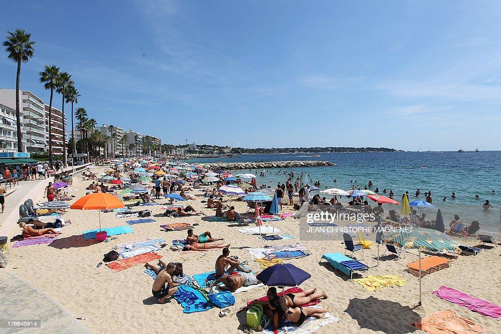 People sunbathe in Antibes, on August 16, 2013, southeastern France.