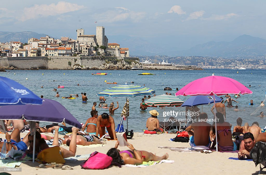 People sunbathe on a beach in Antibes, on August 16, 2013, southeastern France.