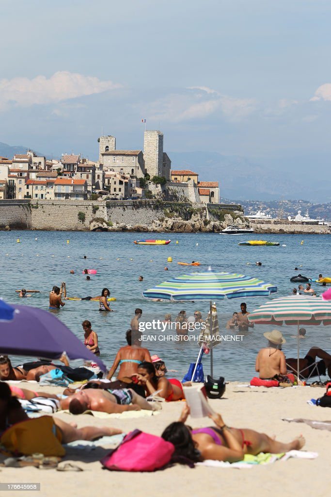 People sunbathe on a beach in Antibes, on August 16, 2013, southeastern France.