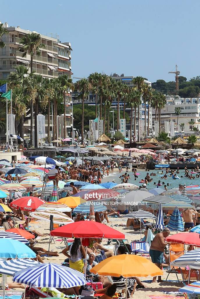 People sunbathe on a beach in Antibes, on August 16, 2013, southeastern France. AFP PHOTO / JEAN CHRISTOPHE MAGNENET