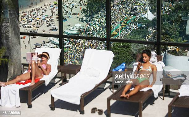 People sunbathe on an upscale hotel rooftop as protesters march below calling for the impeachment of President Dilma Rousseff along Copacabana beach...