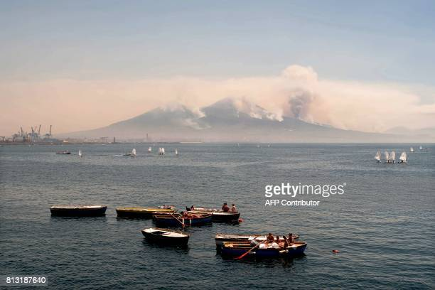 People sunbathe on boats in Naples' harbour as smoke rises from fires on the slopes of the volcano of Mount Vesuvius east of Naples on July 12 2017...