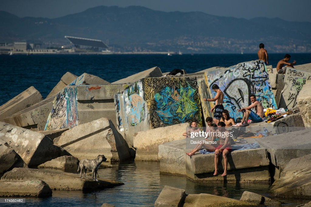 People sunbathe on concrete blocks at Barceloneta Beach on July 24, 2013 in Barcelona, Spain. Foreign visitors to Spain set a new record high in June surpassing six million tourists for the first time ever and climbing by 5.3 percent since June 2012.Ê