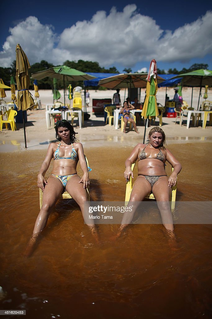 People sunbathe on Praia da Lua beach on Rio Negro a branch of the Amazon River on November 23 2013 in Manaus Brazil Manaus' Arena Amazonia will be a...