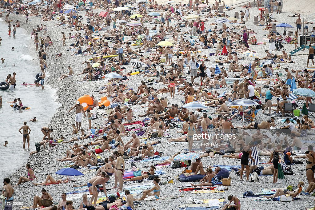 People sunbathe on the beach in the French southeastern ...