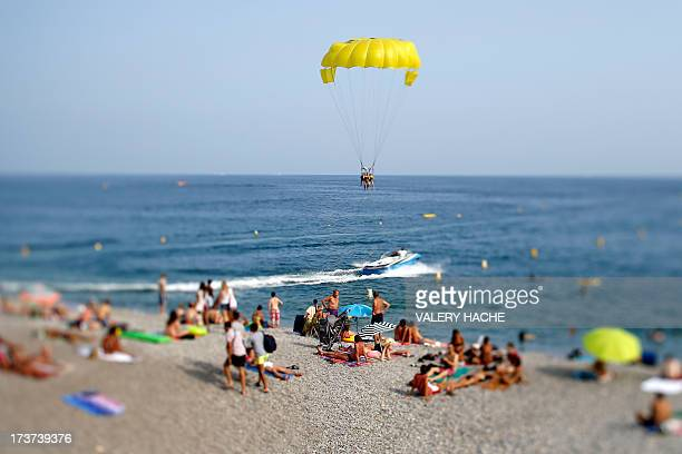 People sunbathe on the beach in the French southeastern city of Nice as others enjoy parasailing on July 17 2013 AFP PHOTO / VALERY HACHE