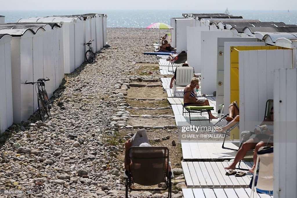 People sunbathe on the beach of Le Havre, northwestern France, on May 27, 2016. / AFP / CHARLY
