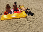 3 people sunbathing in sand with yellow inflatable mattress rimini beach italy 20th july 2015