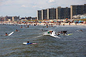 People surf at Rockaway Beach on July 26 2016 in New York City Temperatures are expected to stay in the 90's across most of the Eastern US until this...