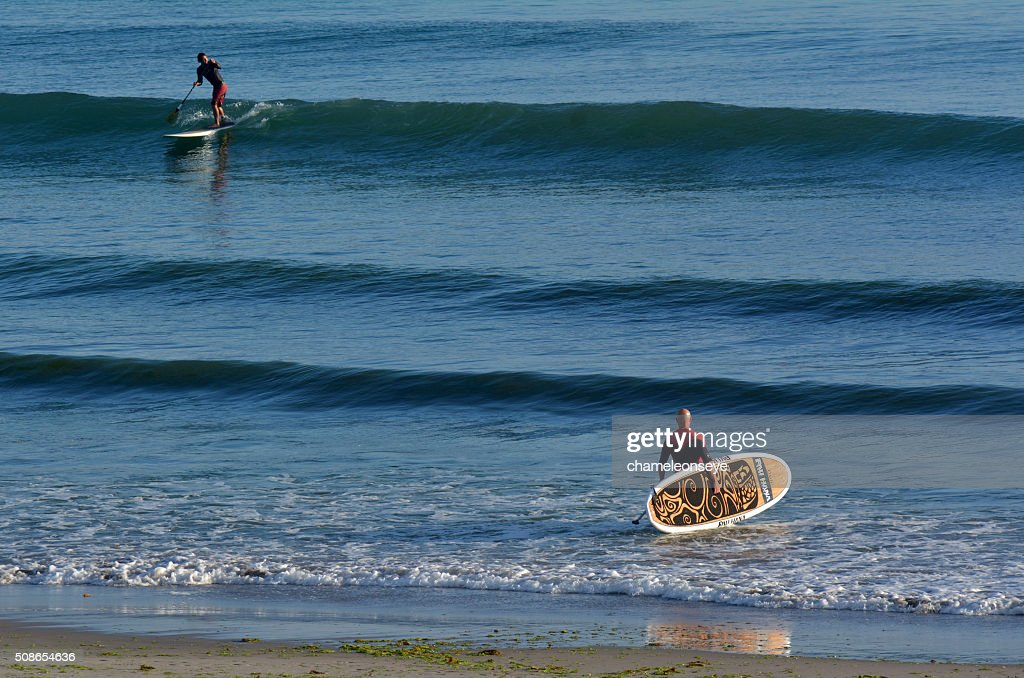 People surf on stand up pedal board : Stock Photo