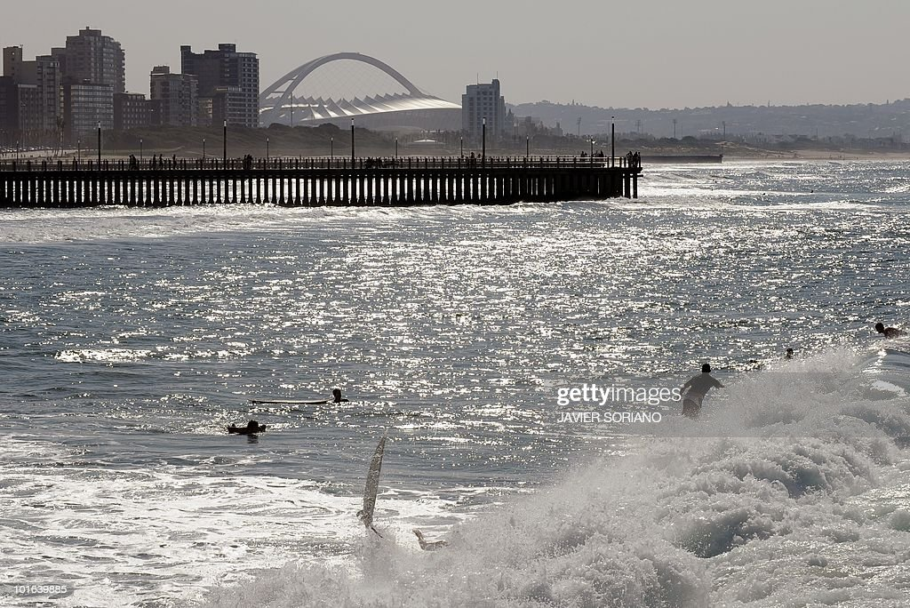 People surf on the beach near the Moses Mabhida Stadium (background) in Durban on June 5, 2010. Seven matches of the South Afruica 2010 World Cup will be held at Mabhida Stadium.