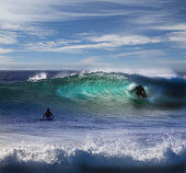 People Surfing at Beach in Waves