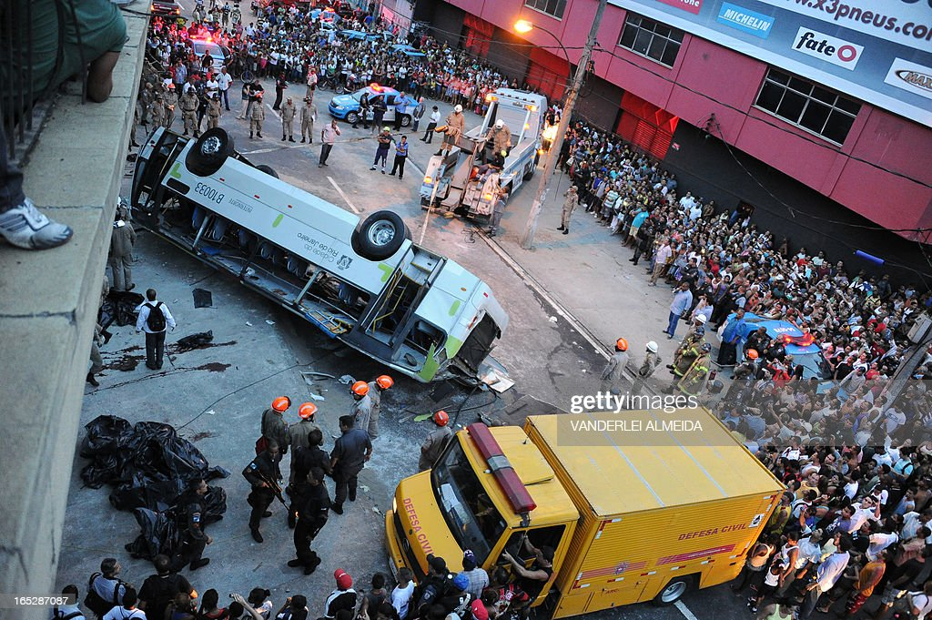 People surround a bus which fell from a bridge with a height of 15 meters in Rio de Janeiro, Brazil on April 2, 2013. The accident left 7 people dead and 11 injured. AFP PHOTO / VANDERLEI ALMEIDA