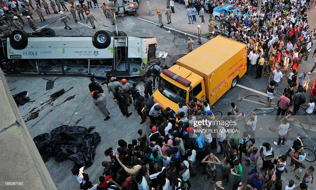 People surround a bus which fell from a bridge with a height of 15 meters in Rio de Janeiro, Brazil on April 2, 2013. The accident left 7 people dead and 11 injured.