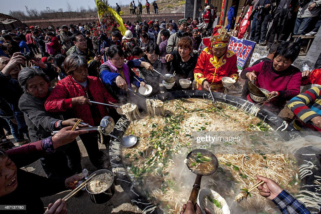 People surround a cauldron to eat noodles at Bailongtan Temple Fair on March 21, 2015 in Anyang, Henan province of China. Each year on Dragon Heads-raising Day, people throughout the country celebrate in different traditions and in Fucheng Village more than 2,000 people eat noodles in the belief that it could eliminate disease.