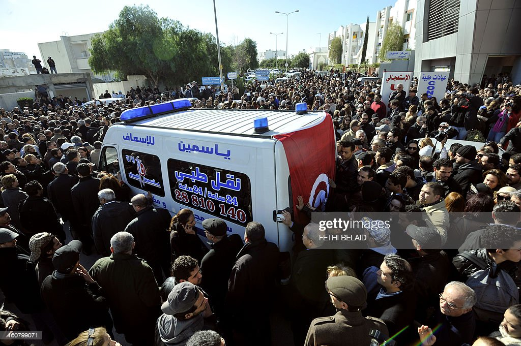 People surround an ambulance transporting the body of Tunisian opposition leader and outspoken government critic Chokri Belaid, from from a clinic in Tunis to the public hospital for an autopsy, after he was shot dead with three bullets fired from close range, on February 6, 2013. Tunisian Premier Hamadi Jebali called the assassination 'an act of terrorism', as the country grapples with growing political instability.