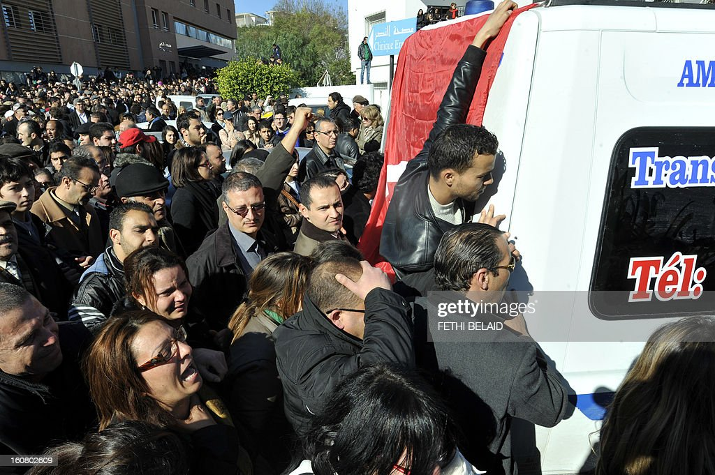 People surround an ambulance transporting the body of Tunisian opposition leader and outspoken government critic Chokri Belaid, from a clinic in Tunis to the public hospital for an autopsy, after he was shot dead with three bullets fired from close range, on February 6, 2013. Tunisian Premier Hamadi Jebali called the assassination 'an act of terrorism', as the country grapples with growing political instability. AFP PHOTO / FETHI BELAID