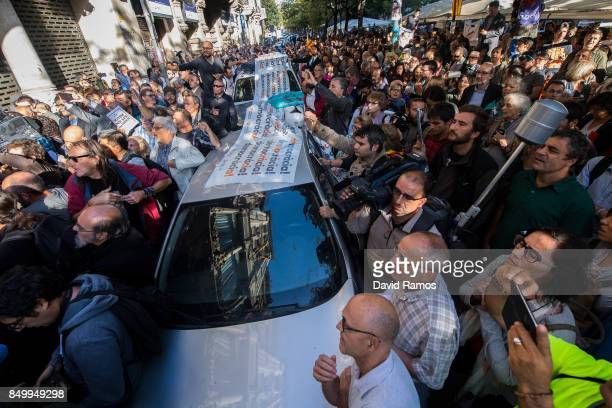 People surround Spanish Civil Guard Police cars outside the Catalan VicePresident and Economy office as police officers hold a searching operation...